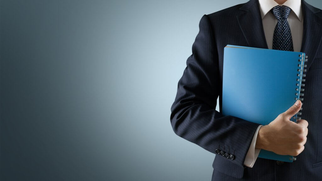 Man in a business suit with a blue notebook against a blue background