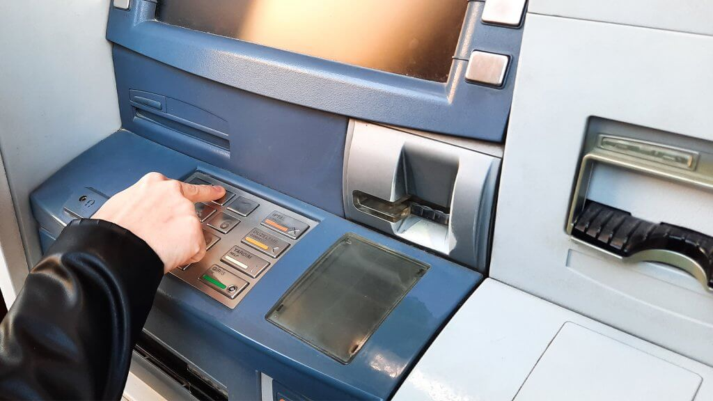 Close up of a person's hand as they use an ATM