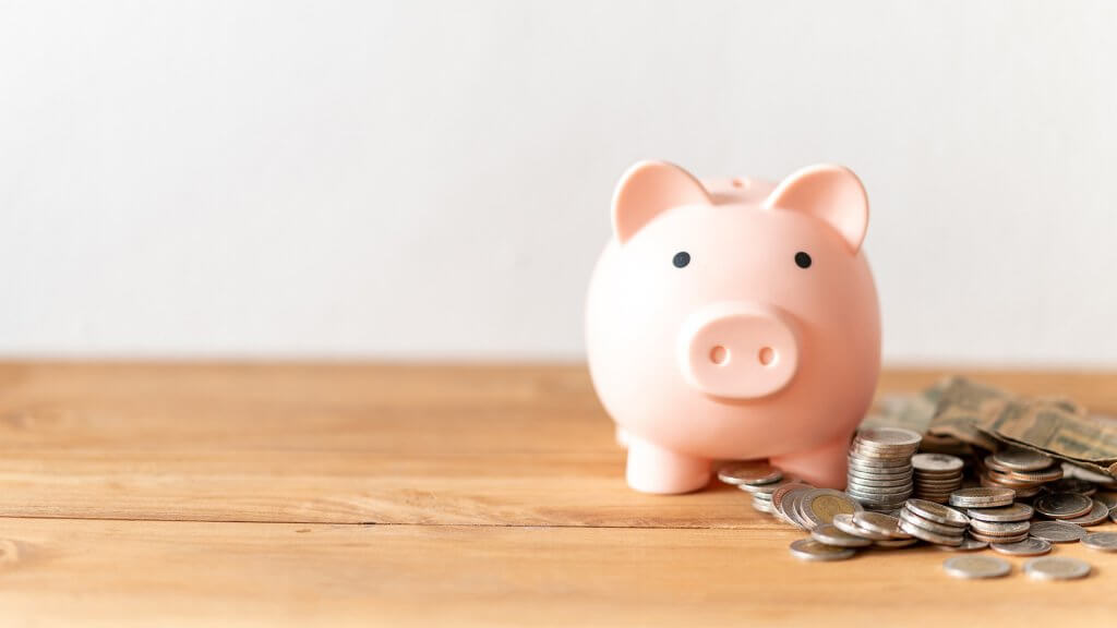 A pink piggy bank wirth coins around it, sitting on a wooden surface