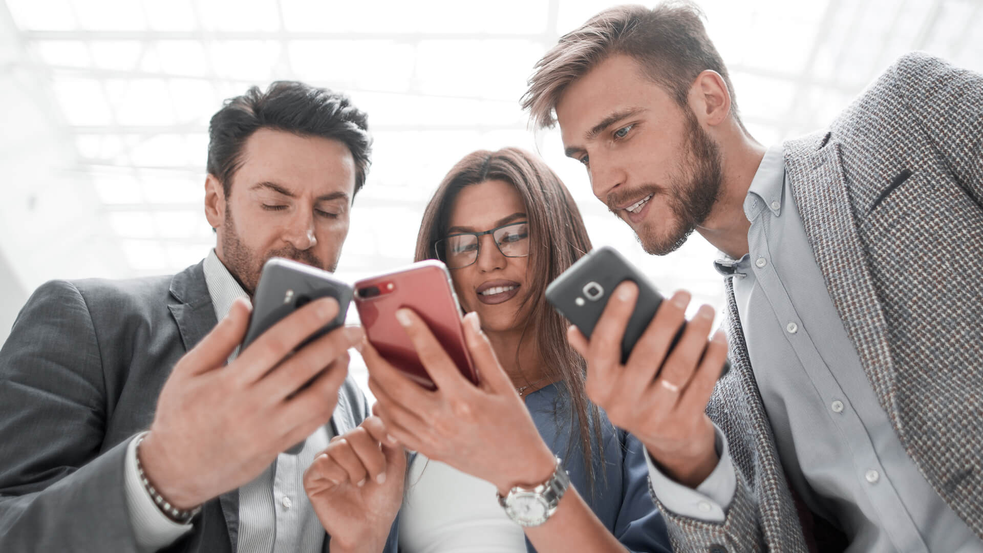 Three young work colleagues stood together, looking at their phones and smiling