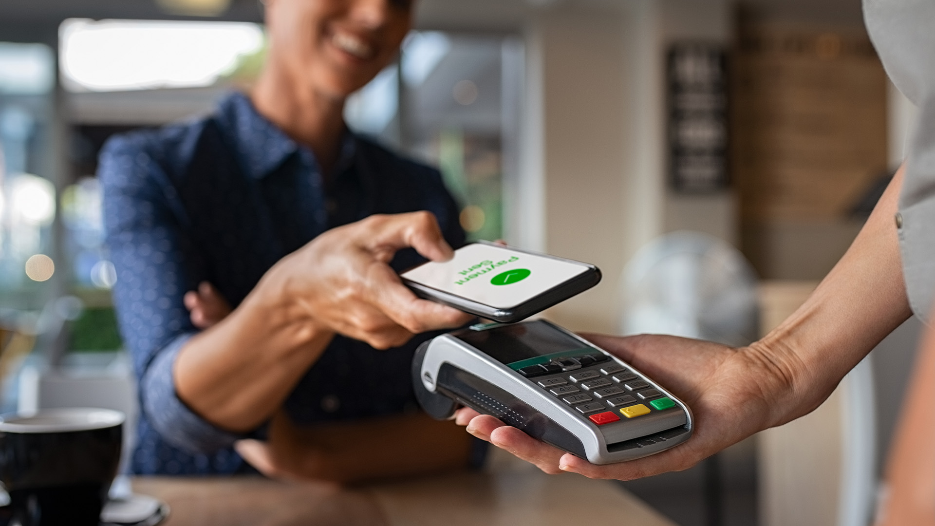 Woman in a cafe paying contactless through mobile on a card machine